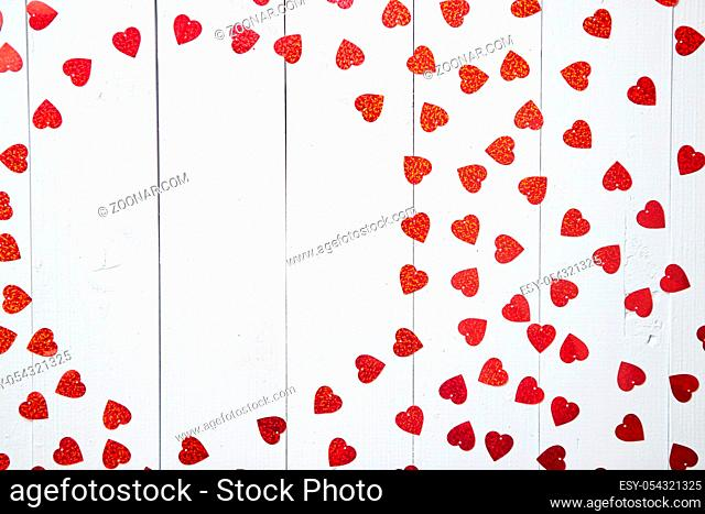Valentine's Day decoration composition. Heart shaped red sequins placed on white wooden table. Frame with copy space. Romantic background