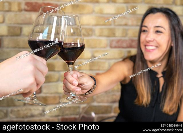 Close up of young couple toasting with glasses of red wine at restaurant. High quality photo