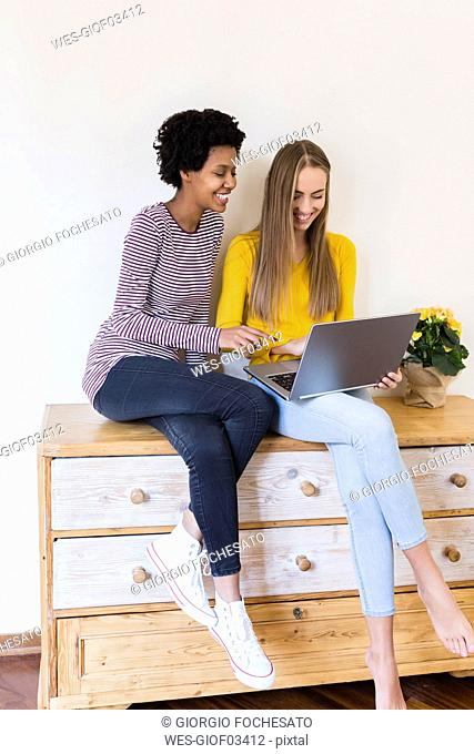 Two young women sitting on cupboard looking at laptop together