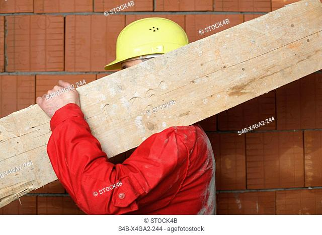 Building worker carrying a board on his shoulder