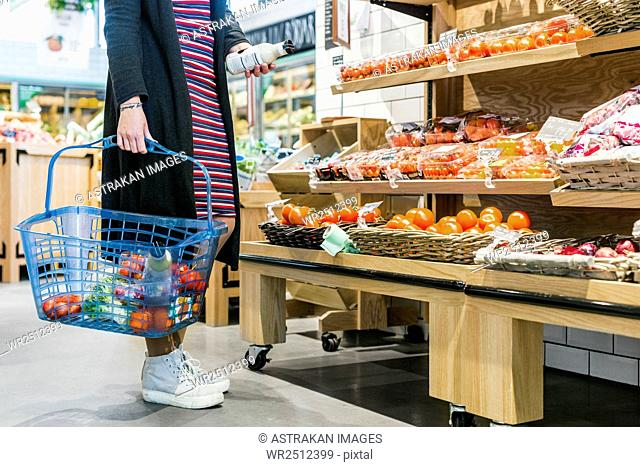 Low section of woman holding basket while shopping in supermarket