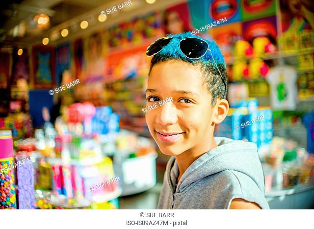 Portrait of teenage boy with blue dyed hair in front of candy stall, Brooklyn, USA