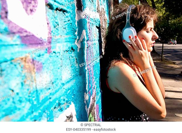 A vintage dressed girl listing to music in a urban environment