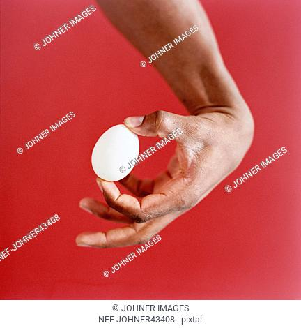 Hand holding egg against a red background