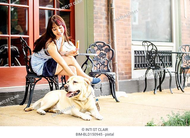 Caucasian woman petting dog at sidewalk cafe
