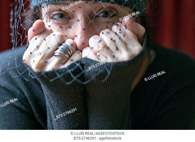 Close-up portrait of mature woman with veil looking at camera, hands covering mouth
