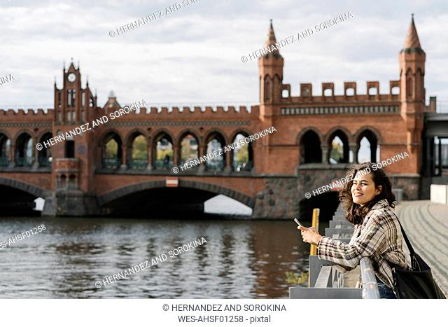 Woman with smartphone in the city at Oberbaum Bridge, Berlin, Germany