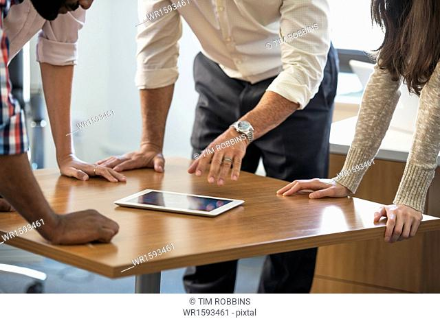 Four people leaning on a table at a meeting, looking at a digital tablet
