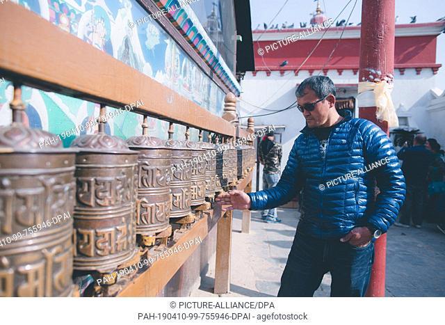 30 January 2019, Nepal, Kathmandu: Lhakpa Gelu Sherpa, 52-year-old mountain guide from Nepal, turns prayer wheels at the Buddhist monastery