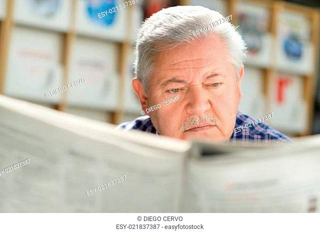 Elderly man with mustache reading paper in library