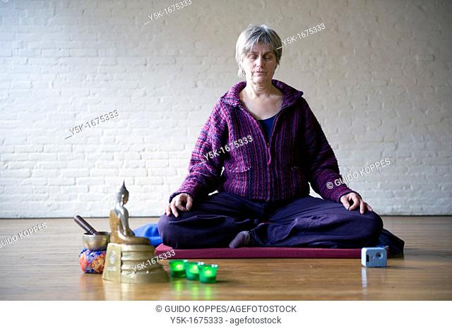Older woman, meditating in an empty room, using Buddhist techniques