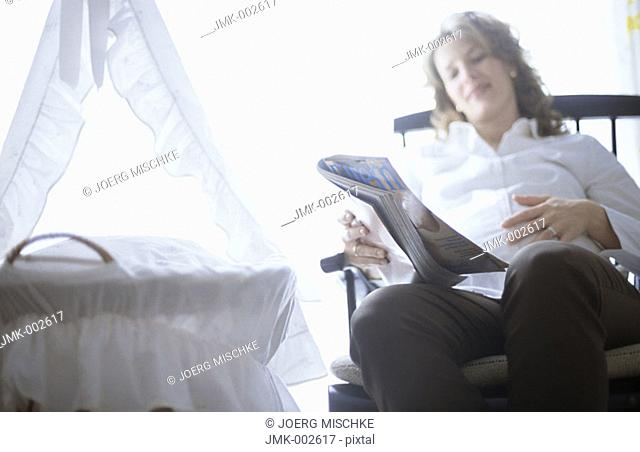 A young pregnant woman, 25-30 30-35 35-40 years old, sitting in a rocking chair in the nursery, next to the cradle, reading