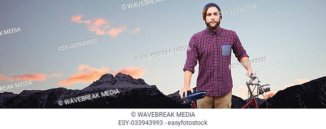 Millennial man with bicycle against mountain tops and evening sky
