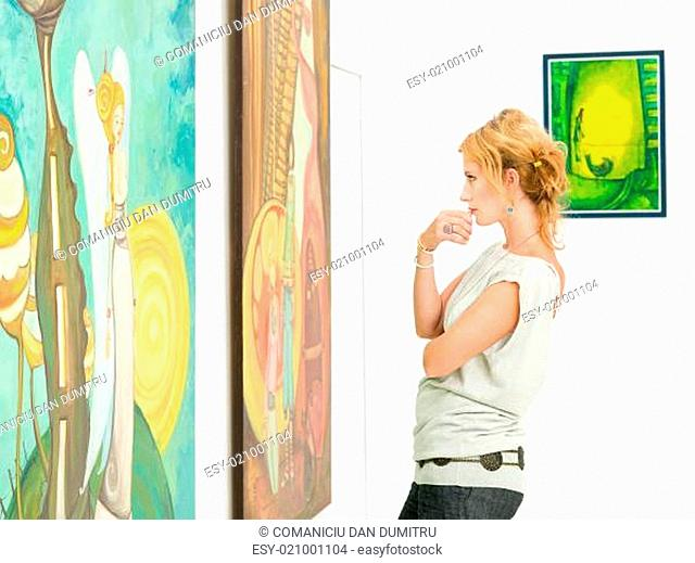 woman contemplaing colorful paintings