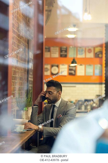 Businessman talking on smart phone, working in cafe