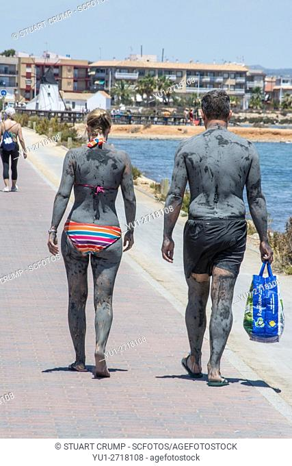 Couple covered in mud from the Mar Menor walk along the jetty at Lo Pagan in Murcia