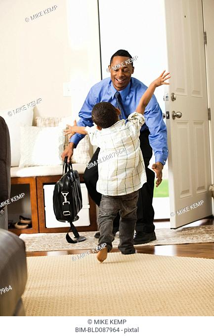 Businessman returning from work being greeted by son