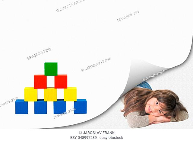Blank white page with curl effect and smiling cute little girl lying in an exposed corner looking at the camera. Pyramid of colorful wooden toy cubes on the...