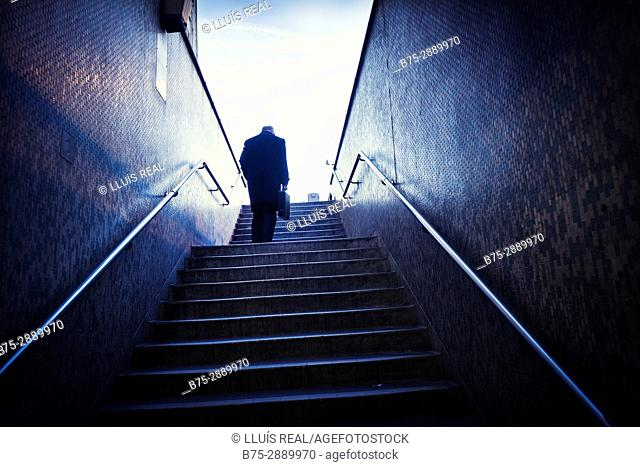 Low angle view of unrecognizable man with briefcase climbing stairs. London Bridge, London, England