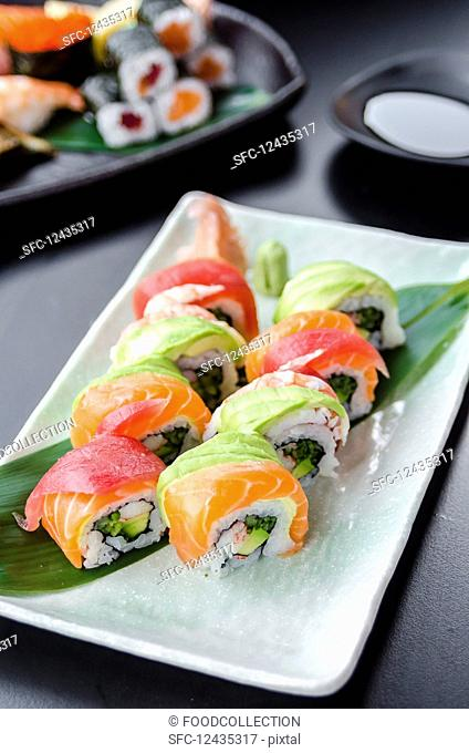 Japanese platter of rainbow rolls maki, inside out seaweed and rice roll filled with cucumber, mayonnaise, avocado, crub stick topped with fresh salmon, tuna