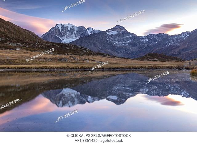 Reflection of the Fletschhorn in a small pond at the top of the Simplon pass at sunset. Simplonpass, Canton of Valais, Switzerland