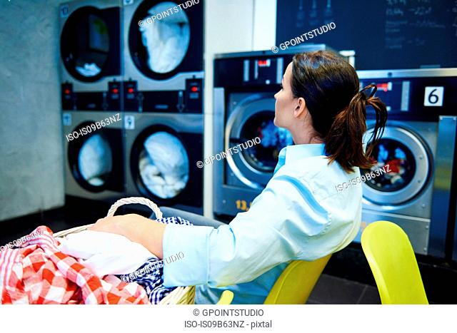 Woman sitting in laundrette staring