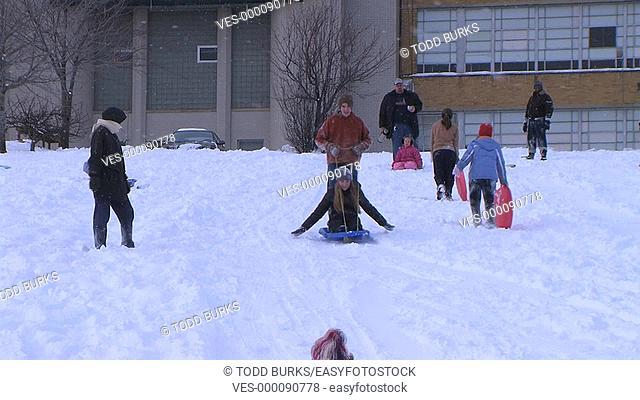 Teenagers sledding down hill and crashing