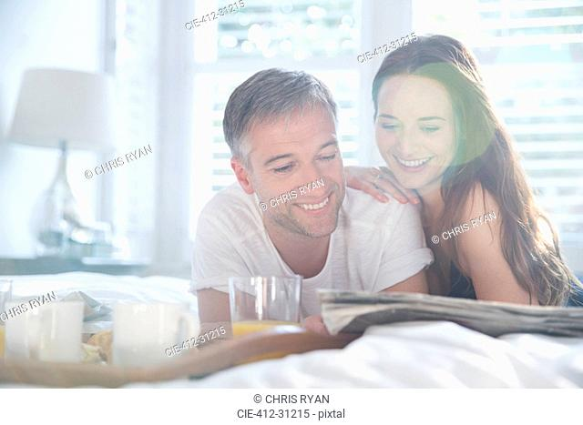Smiling couple reading newspaper in sunny bedroom