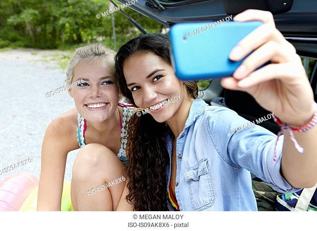 Hikers sitting at rear of car taking selfie