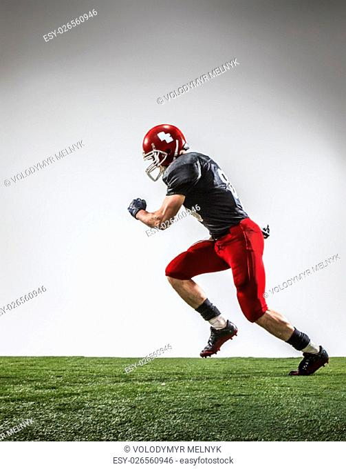 The american football player in action on green grass and gray background