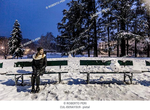 Woman sitting on park bench in covered park in the evening