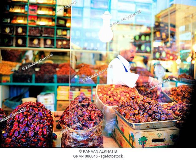 Merchant arranging his dates on display in his shop in Bab Makkah, Jeddah, Saudi Arabia