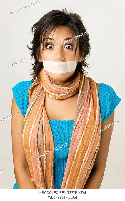 Latin model in her 20s with taped mouth looking surprised