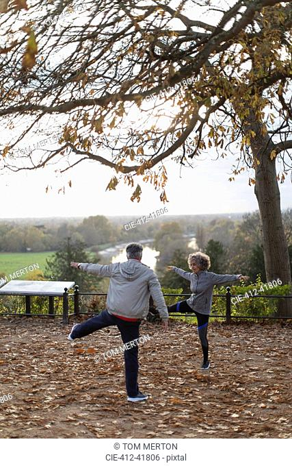 Active senior couple exercising, stretching in autumn park