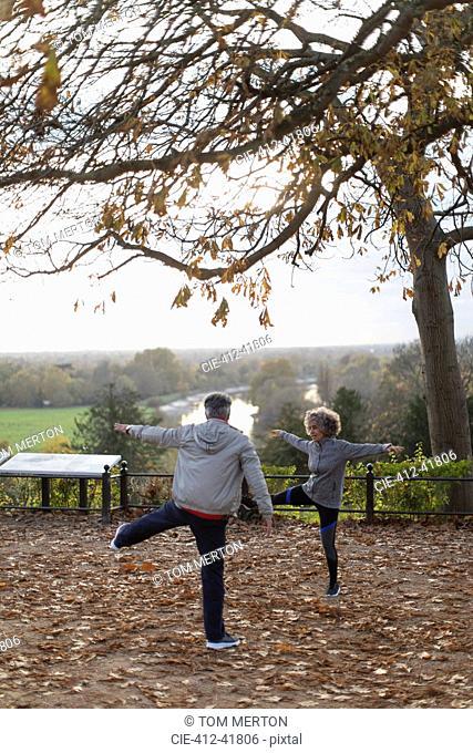 Active senior couple exercising, stretching in autumn park