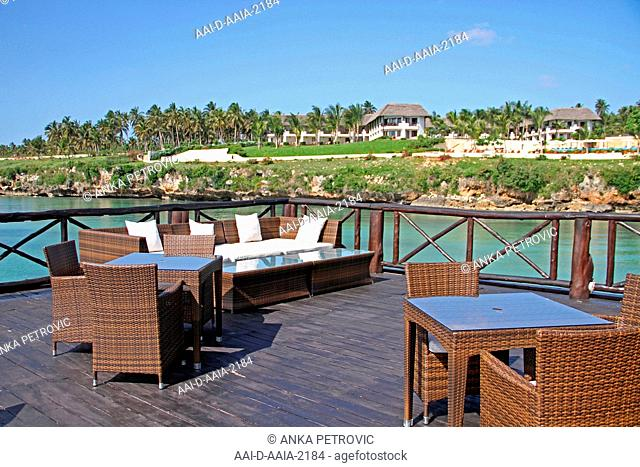 A coffee table and couch on a balcony of the Sea Cliff Resort and Spa Hotel bar and other residence buildings along the Eastern Coast of zanzibar on the shore
