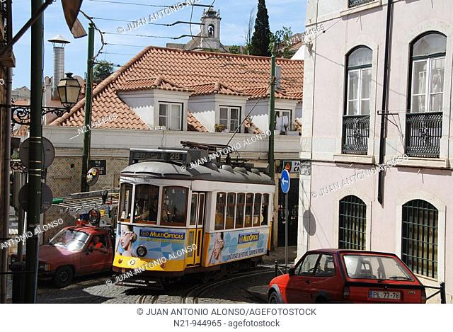 The popular tram 28 through the winding and narrow streets of Alfama. In the background, the towers of  the Mosteriro de Sao Vicente de Fora