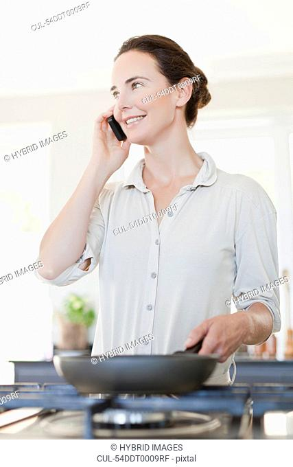 Woman on cell phone cooking