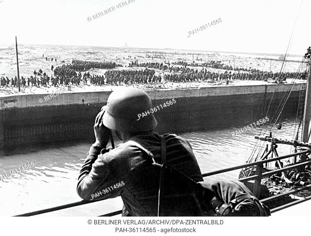 A member of the German Wehrmacht looks through a pair of binoculars on French and British prisoners of war in the harbour of Dunkirk on the Western Front in...