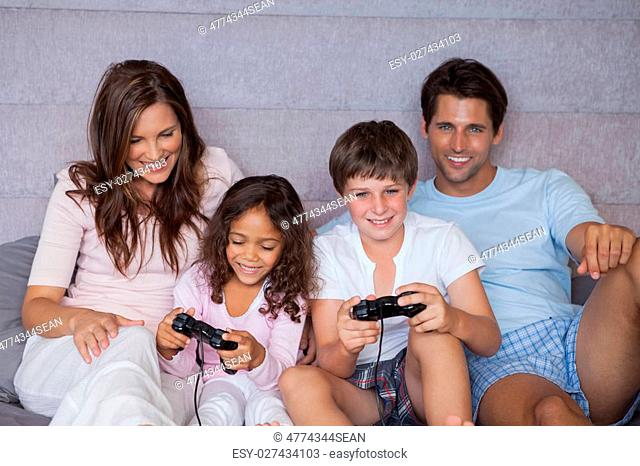 Smiling family playing video games on bed