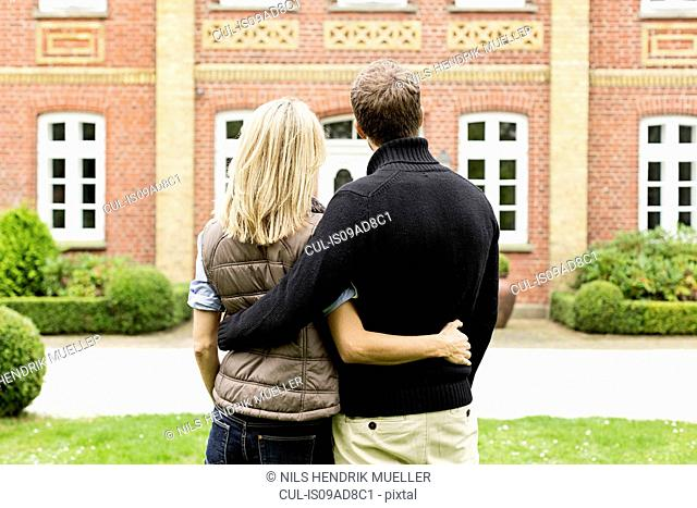 Mid adult couple looking at house, rear view