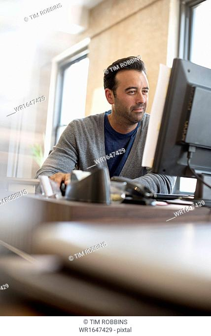 Office life. A man seated at a desk using a computer