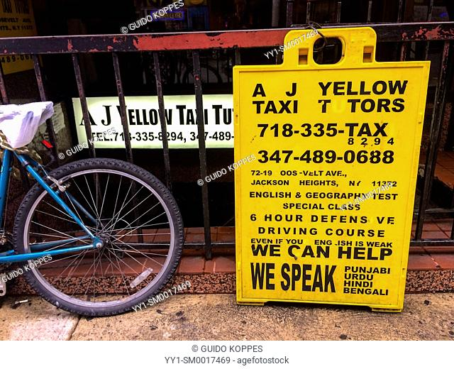 New York City, USA. Advertising sign for taxi driver training with a bike on a fence