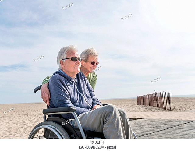 Senior man in wheelchair with wife at beach, Santa Monica, California, USA