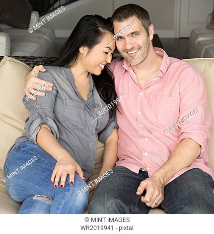 Smiling man and woman sitting on a sofa, hugging, and looking at the camera