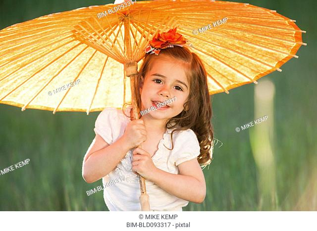 Caucasian girl holding parasol