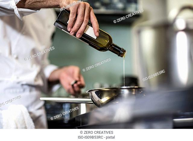 Chef pouring oil into frying pan