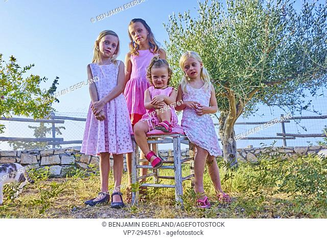 four sibling girls standing together outside in nature garden. Australian ethnicity. During holiday stay in Hersonissos, Crete, Greece