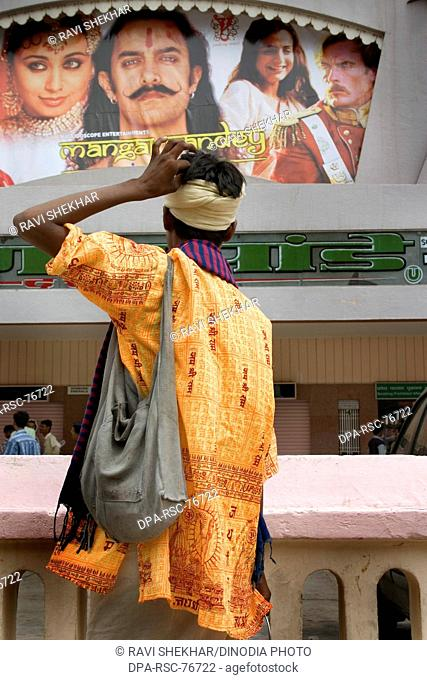 A orange clad religious sadhu looking at  the poster at Raj Mandir cinem hall; movie theater ; showing 'Mangal Pandey-the rising'; Aamir Khan acted as the lead...