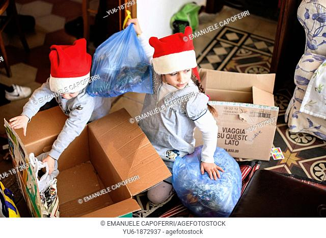 Children with hat of Santa Claus take bags with Christmas decorations, to decorate the house